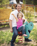 Father and daughter on playground spring rider Royalty Free Stock Image