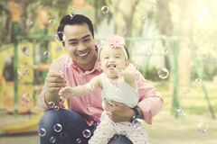 Father and daughter playing bubbles in playground. Father and daughter having a great time with soap bubbles in a playground Royalty Free Stock Image