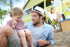Father and daughter playing in camp, mother relaxing Stock Image