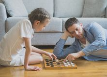 Family playing checkers board game. Father and daughter playing checkers board game royalty free stock photo