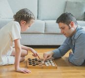 Family playing checkers. Stock Image
