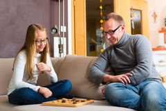 Father and daughter playing checkers Stock Photo