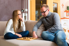 Father and daughter playing checkers Royalty Free Stock Photography