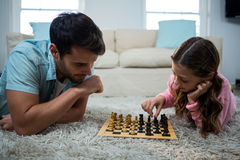 Father and daughter playing chess in the living room Royalty Free Stock Images