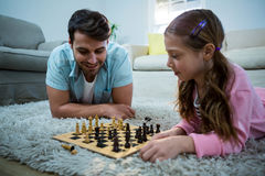 Father and daughter playing chess in the living room Stock Image