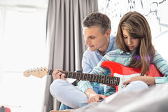 Father and daughter playing electric guitar at home Stock Photo