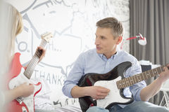 Father and daughter playing electric guitars at home Stock Image