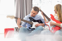 Father and daughter playing electric guitars at home royalty free stock photography