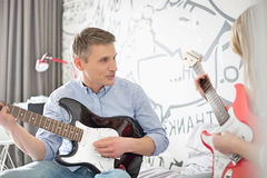Father and daughter playing electric guitars at home Royalty Free Stock Image