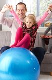 Father and daughter playing with fit ball at home royalty free stock images