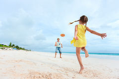 Father and daughter playing with flying disk. At beach Stock Image