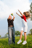 Father and daughter playing football on meadow Stock Images