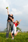 Father and daughter playing football on meadow Stock Photos