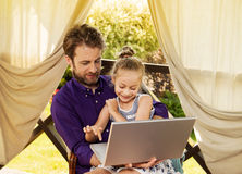 Father and daughter playing game on laptop computer in the garden Stock Image