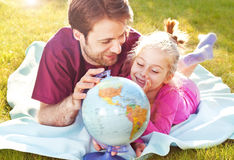 Father and daughter playing globe in the garden. Father and daughter playing globe while laying outdoor on the grass in the garden during sunset Royalty Free Stock Photos