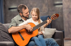 Father and daughter playing guitar royalty free stock images