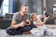 Father and daughter playing with joysticks Royalty Free Stock Image