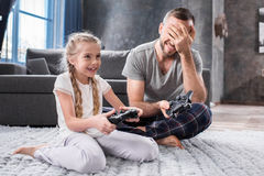 Father and daughter playing with joysticks. Father and daughter sitting on carpet and playing video games with joysticks Royalty Free Stock Images