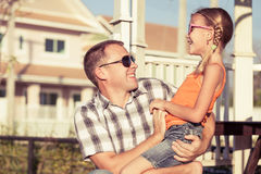 Father and daughter playing near the house at the day time. Stock Photos