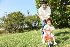 Father and daughter playing in the park. Concept shot of Japanese people's life style Royalty Free Stock Photo