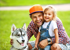Father and daughter playing in the park. In love with Dog Husky royalty free stock photos