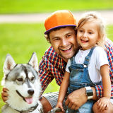 Father and daughter playing in the park. In love with Dog Husky royalty free stock photography