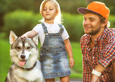 Father and daughter playing in the park. In love with Dog Husky royalty free stock photo
