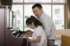 Father and daughter playing the piano royalty free stock photo