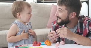 Father and daughter playing with plasticine. Father and cute baby daughter playing with plasticine at home stock video footage