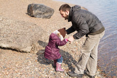 Father and daughter playing on a riverbank Royalty Free Stock Images