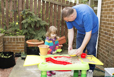 Father and daughter playing at a sand table. A father and small child are playing together at a sand table in a garden setting Royalty Free Stock Photography