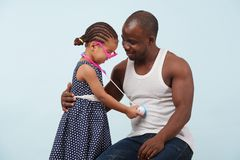 Father and daughter playing with a stethoscope against pale blue background. Happy father and daughter playing doctor with a toy stethoscope against pale blue stock photo