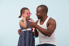 Father and daughter playing with a stethoscope against pale blue background. Happy father and daughter playing doctor with a toy stethoscope against pale blue royalty free stock photo