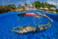 Father and daughter playing in a swimming pool royalty free stock images