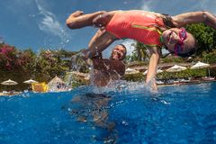 Father and daughter playing in a swimming pool Royalty Free Stock Photo