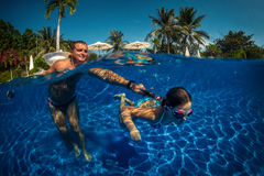 Father and daughter playing in a swimming pool Stock Photo