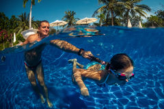 Father and daughter playing in a swimming pool Stock Photography