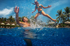 Father and daughter playing in a swimming pool Stock Photos
