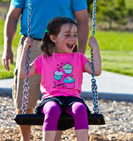 Father and daughter playing on the swing at the park Royalty Free Stock Photography