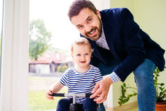 Father and daughter playing together, riding a bike indoors Stock Photo