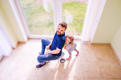 Father and daughter playing together, riding a bike indoors Royalty Free Stock Photography