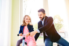 Father and daughter playing together, riding a bike indoors Royalty Free Stock Images