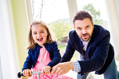 Father and daughter playing together, riding a bike indoors Stock Image