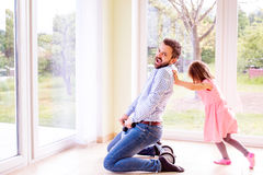 Father and daughter playing together, riding a bike indoors Stock Photos