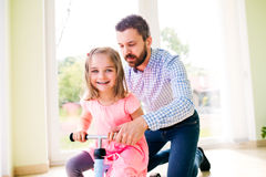 Father and daughter playing together, riding a bike indoors Royalty Free Stock Image