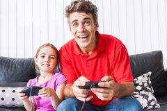 Father and daughter playing video game stock photo