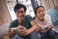 Father and daughter playing video game in living room. At home Stock Photos