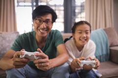 Father and daughter playing video game in living room. At home Royalty Free Stock Image