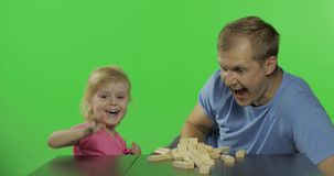 Father and daughter plays the jenga. Little child pulls wooden blocks from tower stock video