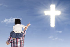 Father and daughter pointing at cross Royalty Free Stock Images